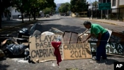 """Man arranges board with spraypainted message that reads """"Carnivals 2014,"""" at a barricade set up by anti-government protesters, Valencia, Venezuela, Feb. 27, 2014."""
