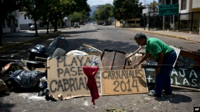 "Man arranges board with spraypainted message that reads ""Carnivals 2014,"" at a barricade set up by anti-government protesters, Valencia, Venezuela, Feb. 27, 2014."