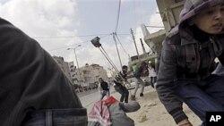Người Palestine ném đá vào binh sĩ Israel ở chốt kiểm soát Kalandiam, nằm giữa Jerusalem và thành phố Ramallah ở bờ Tây, 30/3/12