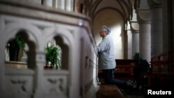 FILE - A woman prays at Sheshan Cathedral in the outskirts of Shanghai, October 28, 2013.