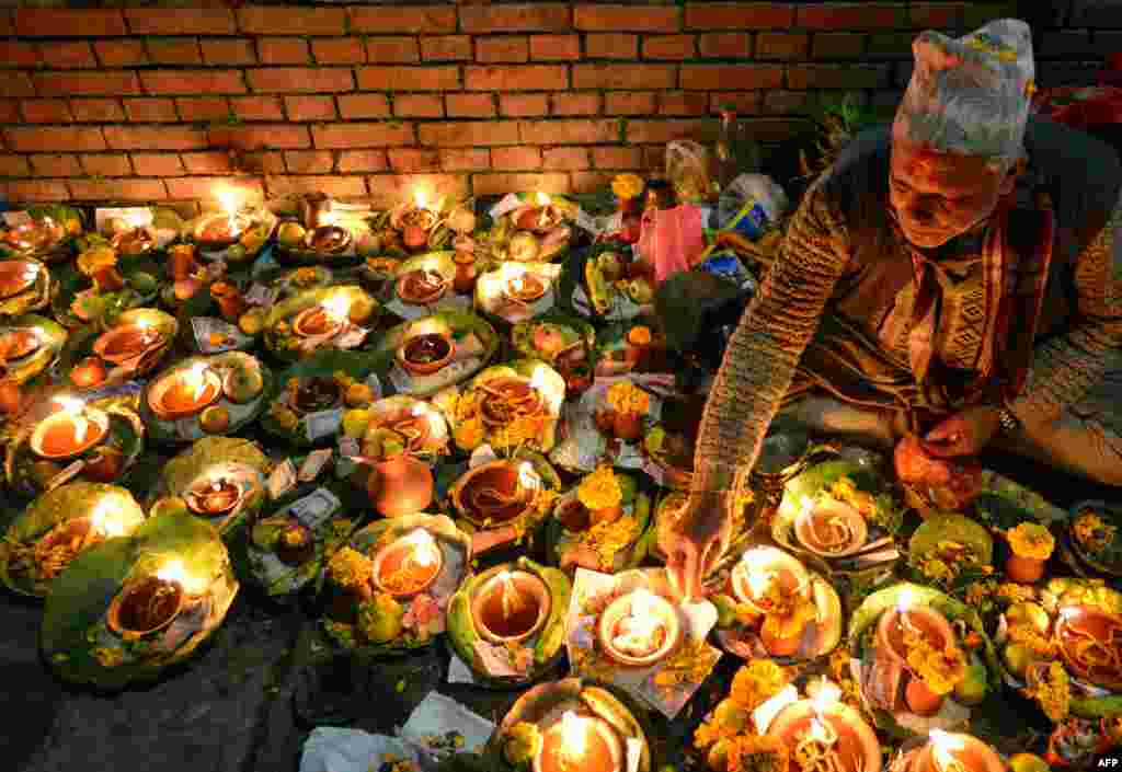 A Hindu devotee lights oil lamp in memory of deceased family members during the Balachaturdashi festival at the Pashupatinath Temple in Kathmandu, Nepal.