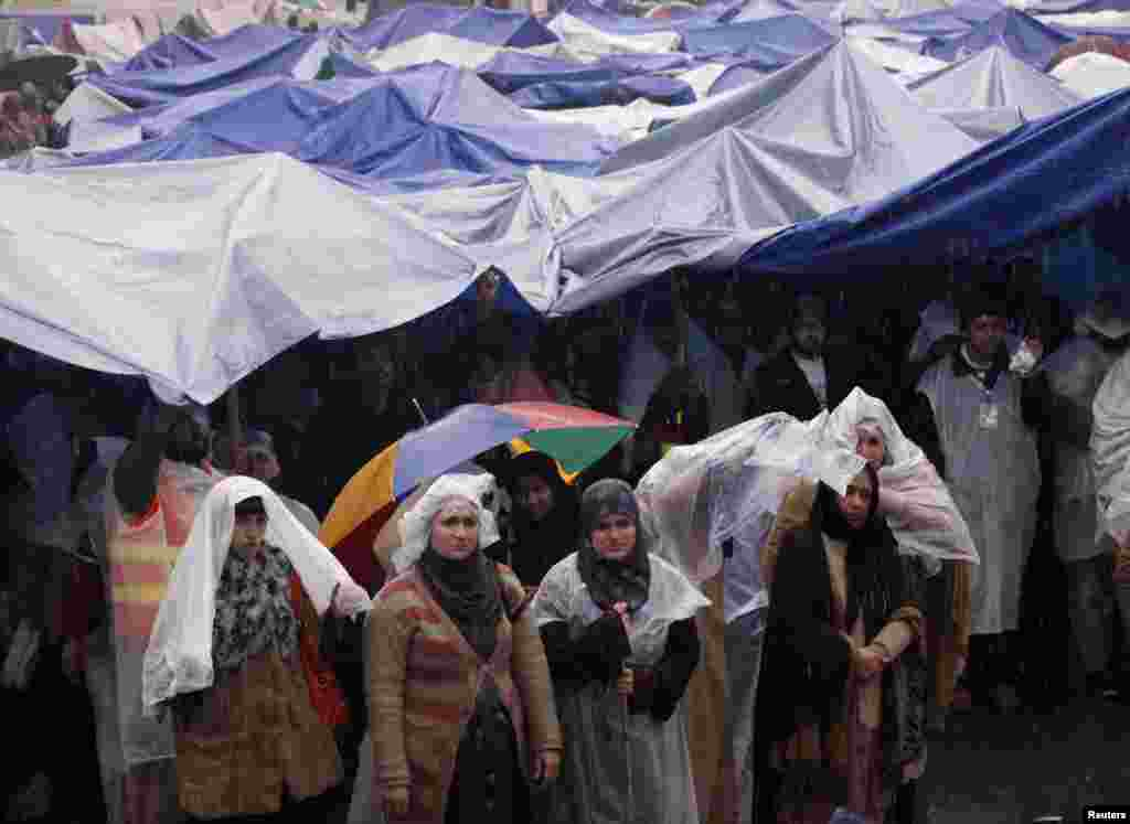 Supporters of Tahir-ul Qadri listen to him while standing in the rain during the fourth day of protest in Islamabad, Pakistan, January 17, 2013.