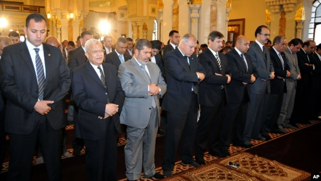 Egyptian President Mohamed Morsi, third left, attends Friday prayers in Cairo, Egypt, April 26, 2013.