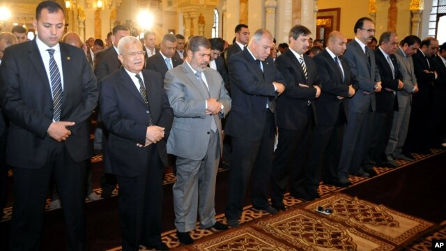 Egyptian President Mohamed Morsi, third left, attends Friday prayers in Cairo, Egypt, April 26, 2013.