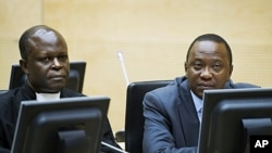 Uhuru Kenyatta (R) and a member of the Defense Council attend a hearing at the International Criminal Court (ICC) in The Hague, September 21, 2011.