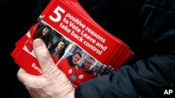 A Pro-Brexit campaigner hands out leaflets at Liverpool Street station in London, Wednesday, March 23, 2016. With less than three months to go until a June 23 referendum, Britain's anti-EU campaigners are bitterly divided, with two rival camps battling over which will be the standard-bearer in the campaign, and over how to win the historic vote. (AP Photo/Frank Augstein)