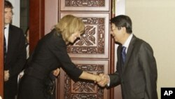 U.N. Under Secretary-General for Legal Affairs, Patricia O'Brien, center, shakes hands with Cambodian Deputy Prime Minister Sok An prior to a meeting in Phnom Penh, Cambodia, Thursday, Oct. 20, 2011. O'Brien was expected to meet with Cambodian government
