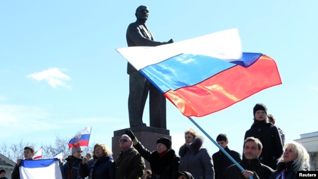 Participants in a pro-Russian rally wave Russian flags in front of a statue of Soviet state founder Vladimir Lenin in Simferopol, March 17, 2014.