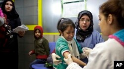 FILE - A Syrian girl cries after being vaccinated against the measles at a U.N. registration center in Zahleh, in Lebanon's Bekaa Valley.