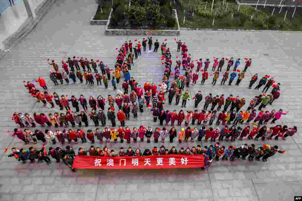 Teachers and students stand in a lotus flower formation to mark the 15th anniversary of the return of the Macau Special Administrative Region to China at a primary school in Lianyungang, east China's Jiangsu province. Chinese President Xi Jinping visited Macau for the anniversary.