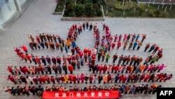 澳門特別行政區成立15周年的慶祝大會,由老師和學生拼出蓮花圖案。