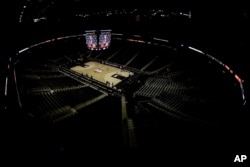 Big 12 commissioner Bob Bowlsby is seen on the big screen in an empty Sprint Center in Kansas City, Mo., as he talks to the media after canceling the remaining NCAA college basketball games in the Big 12 Conference tournament, March 12, 2020.
