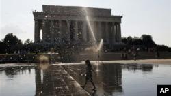 Một bé gái chạy ngang 1 vòi phun nước gần Đài tưởng niệm Lincoln ở Washington, 2/7/2012