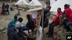 پاکستانی تارکین وطن یونان میں ایک کیمپ میں اپنے موبائل فون چارج کر رہے ہیں۔ فائل فوٹو