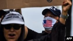 "Seorang pendukung Presiden Donald Trump (kanan) mengenakan masker wajah dalam ""Pawai Kebebasan"" untuk menuntut pencabutan karantina wilayah terkait wabah virus corona di Florida, South Beach, Miami, 10 Mei 2020."