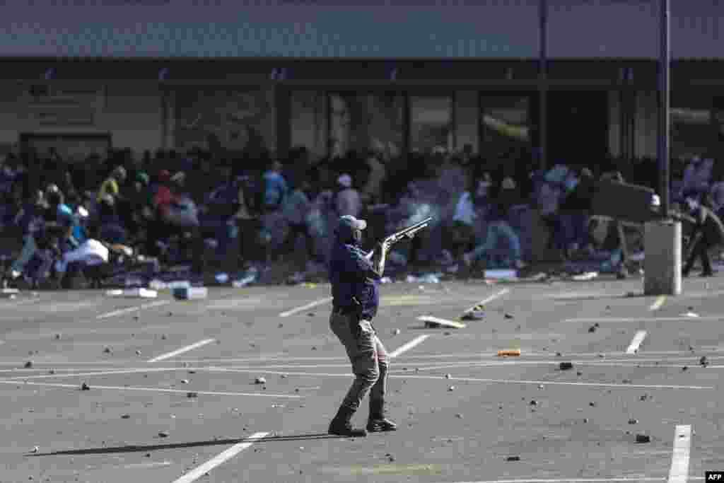 Cənubi Afrika Polis Jabulaniticarət mərkəzini qarət edən qiyamçılara rezin güllələr atır
