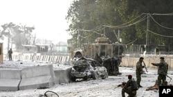 阿富汗士兵2月27日检查喀布尔郊外一个机场入口的自杀炸弹爆炸现场