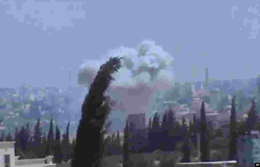 In this image taken from video obtained from the Shaam News Network, columns of smoke billow after heavy bombing, in the countryside outside of Aleppo, Syria, July 22, 2013.