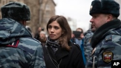 FILE - Member of the Pussy Riot punk group, Nadezhda Tolokonnikova (C) speaks to a police officer outside Zamoskvoretsky District Court in Moscow, Russia, Feb. 24, 2014.