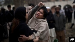 A grieving woman is comforted outside a hospital morgue, where the bodies of victims of a twin suicide bombing were taken, Islamabad, March 3, 2014.