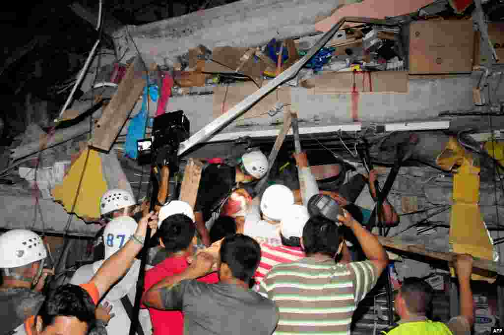 Rescue workers work to pull out survivors trapped in a collapsed building after a huge earthquake struck, in the city of Manta, April 17, 2016.