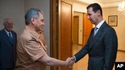 Presiden Suriah Bashar al-Assad berjabat tangan dengan Menteri Pertahanan Sergei Shoigu di Damaskus (18/6).