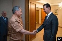 Syrian President Bashar al-Assad shakes hands with Russian Defense Minister Sergei Shoigu in Damascus, June 18, 2016.
