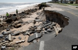 Officials photograph sections of highway A1A that were washed out by Hurricane Matthew, Oct. 8, 2016, in Flagler Beach, Florida.