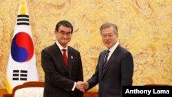 문재인 한국 대통령(오른쪽)이 11일 청와대에서 방한 중인 고노 다로 일본 외무상을 만나 악수하고 있다.