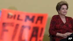 """Brazil's President Dilma Rousseff attends having in front a poster written in Portuguese """"Dilma Stay, during ceremony of the Launch Program New Federal Universities, at the Planalto Presidential Palace, in Brasilia, May 9, 2016."""