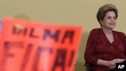 """Presiden Brazil Dilma Rousseff di depan poster bertuliskan """"Dilma Bertahanlah"""" dalam sebuah upacara peluncuran program pendidikan di Istana Kepresidenan Planalto di Brasilia (9/5). (AP/Eraldo Peres)"""