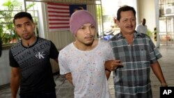 Wee Meng Chee, center, a Malaysian rapper popularly known as Namewee, is escorted by plainclothes policemen as he arrives at the magistrate court in Penang, Malaysia, Monday, Aug. 22, 2016.