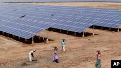 Indian laborers work near solar panels at a Solar Park in India.
