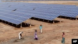FILE - Indian laborers work near solar panels at the Gujarat Solar Park at Charanka in Patan district, about 250 kilometers (155 miles) from Ahmadabad, India.
