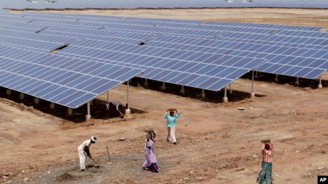 Indian laborers work near solar panels at the Gujarat Solar Park at Charanka in Patan district, about 250 kilometers (155 miles) from Ahmadabad, India, Apri. 14, 2012.