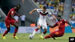 Germany's Mesut Ozil, center, is challenged by Ghana's Sulley Muntari, right, during the group G World Cup soccer match at the Arena Castelao in Fortaleza, Brazil, June 21, 2014.