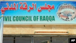 FILE - A sign for the Civil Council of Raqqa is seen on a building in Ain Issa on the northern outskirts of the former self-proclaimed Islamic State capital in Syria, July 23, 2017.