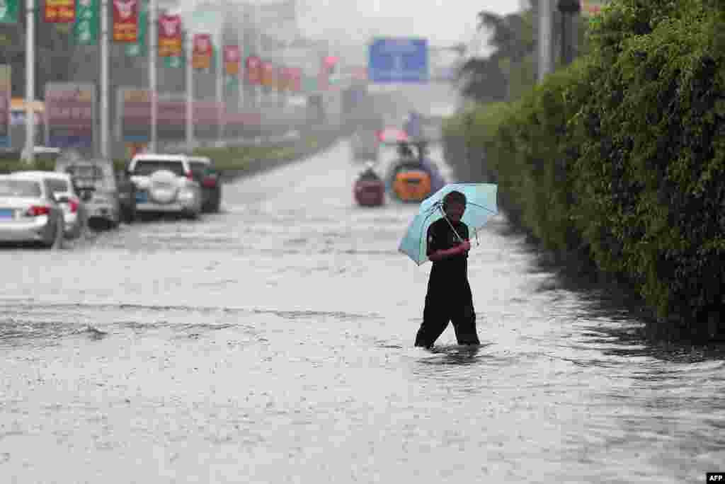 A man walks on a flooded street as typhoon Matmo made landfall, Jinjiang, Fujian province, China, July 23, 2014.
