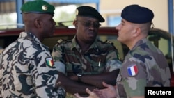 A French army officer (R) talks to his Malian and Senegalese army counterparts outside where a meeting is taking place for the intervention force provided by the ECOWAS grouping of West African states, in Bamako January 15, 2013.