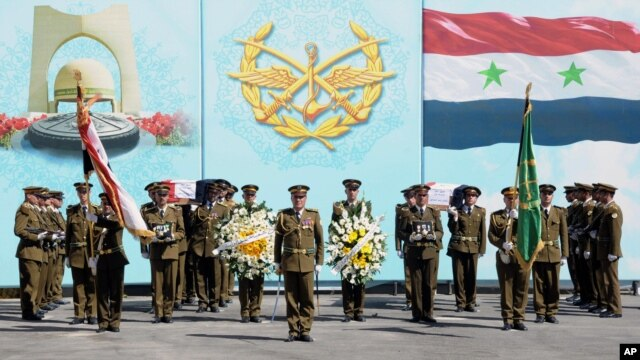 In this photo released by the Syrian official news agency SANA, Syrian honor guard soldiers carry the coffins of Syrian army soldiers who were killed in recent violence in the country, during their funeral procession at the military hospital, in Damascus,