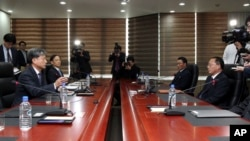 Hwang Boogi, left, South Korea's vice minister of unification and the head negotiator for high-level talks with North Korea, talks as his North Korean counterpart Jon Jong Su, right, listens during their meeting, Dec. 11, 2015.