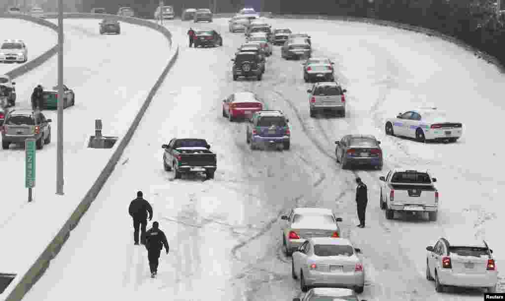 A policia de Charlotte Mecklenburg presta assistencia aos automobilistas numa estrada completamente coberta por neve em Charlotte, Carolina do Norte, Fev. 12, 2014.