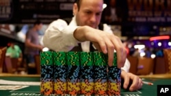 FILE - A dealer adjusts a stack of chips before the first day of the World Series of Poker main event, a Texas hold 'em competition, in Las Vegas, Nov. 10, 2014.