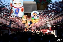 "Visitors walk underneath New Year's Day decorations celebrating next year's ""Year of the Dog"" from the Chinese zodiac at the Nakamise shopping alley, the front approach to Sensoji Temple, in Tokyo, 2017."