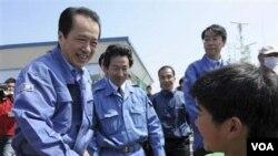 Perdana Menteri Jepang Naoto Kan (kiri) menjabat tangan seorang anak laki-laki di Ishinomaki, salah satu daerah yang terkena dampak parah bencana.