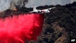 Pesawat pemadam kebakaran menjatuhkan zat pemadam untuk mengendalikan kebakaran hutan dekat Bradbury, California (22/6). (AP/Nick Ut)