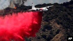 Sebuah pesawat pemadam kebakaran berusaha memadamkan kebakaran kawasan hutan di Bradbury, California (22/6).