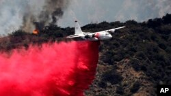 A firefighting aircraft makes a low-altitude pass to drop fire retardant to battle a wildfire near Bradbury, Calif., June 22, 2016