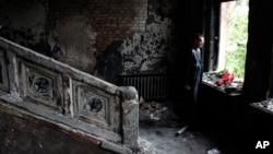 5月4日一名男子在被烧毁的奥德萨市工会大楼内鲜花悼念死者