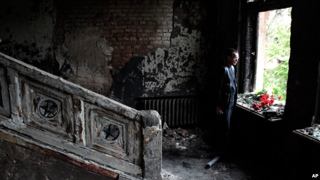 A man lays flowers inside the burnt-out Trade Unions Building in Odessa, Ukraine, May 4, 2014.